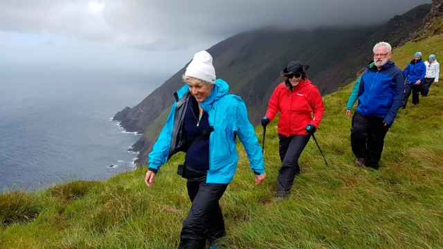 Happy hikers striding over a 2000 foot drop beneath the holy Mount Brandon, Dingle Peninsua, County Kerry